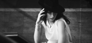 bella hadid posing with hand on face and wearing a black hat
