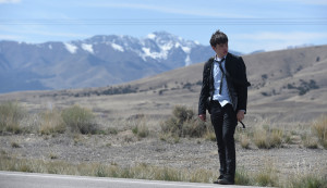 Nick Robinson wearing a suit, tie and backpack on roadside, being charlie movie