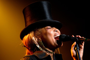 female performer singing into a microphone and wearing a top hat