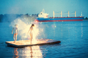 RYAN MCGINLEY, naked woman and man standing in sparklers on the water with a boat in the distance