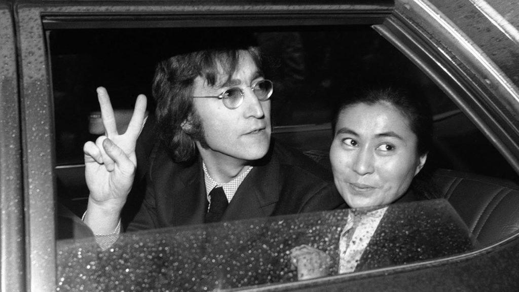 John Lennon Peace sign in car and Yoko Ono