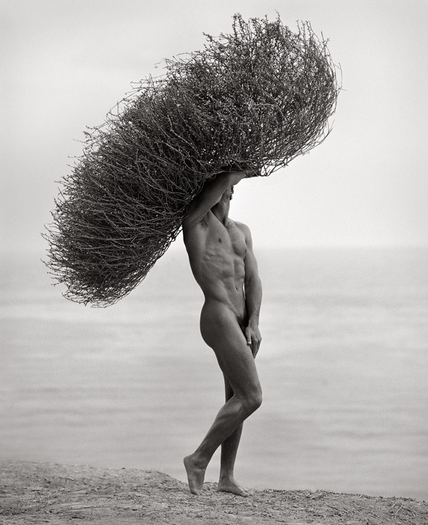 Nude male on beach with seaweed crown by Herb Ritts