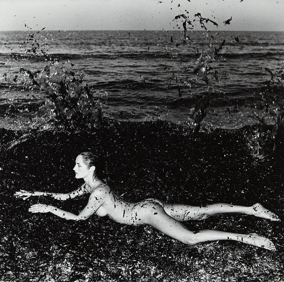 nude woman on beach by Helmut Newton
