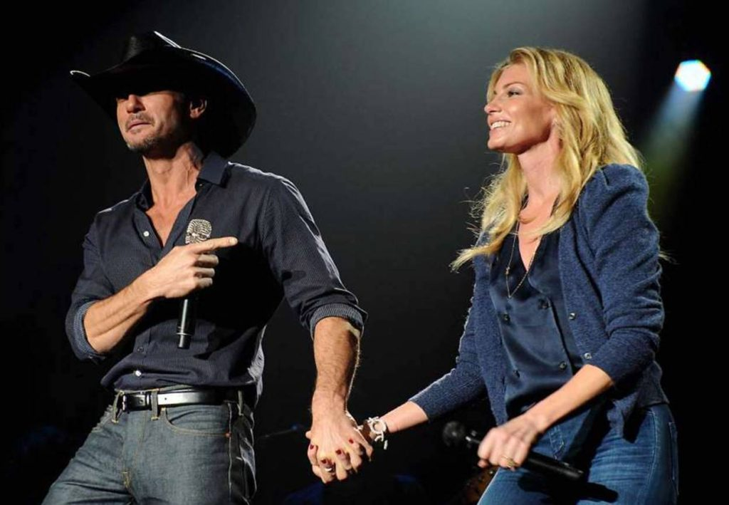 Tim Mcgraw and Faith Hill holding hands on stage