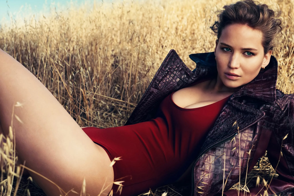 Jennifer Lawrence in red body suit sitting in wheat field