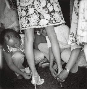 Black and white photograph of model back stage having shoes put on her feet shot by Lee Friedlander
