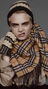 Cara Delevigne wearing a burberry scarf and snarling at the camera