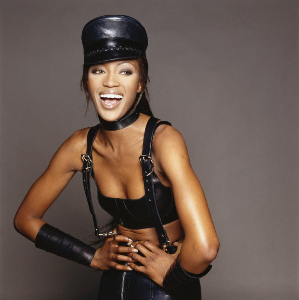 Naomi Campbell Wearing Black Leather S & M Hat, Arm Guards and Leather Bra