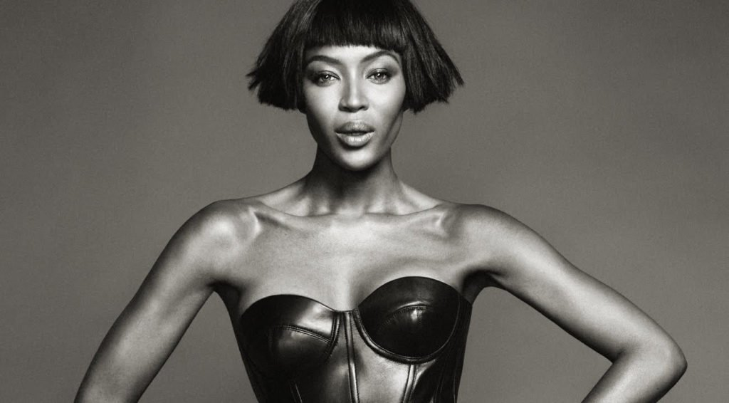 Black and white photograph of Naomi Campbell wearing a black leather bustier
