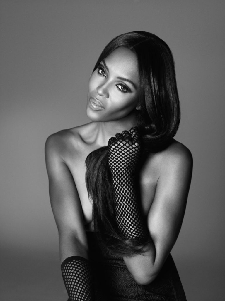 Black and white photograph of Naomi Campbell wearing black fishnet gloves