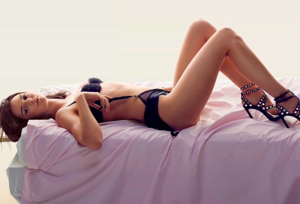 Sexy photograph of Kendall Jenner lying on a pink sheet wearing black bra, panties and black studded stilletos