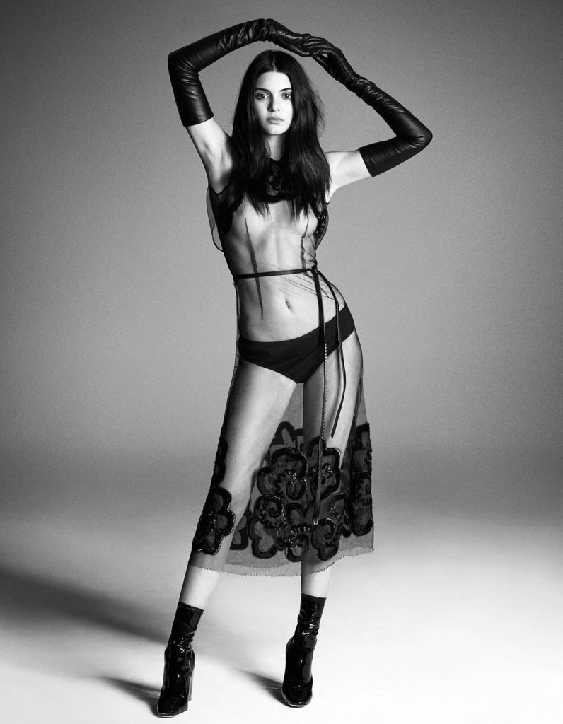 Sexy black and white photograph of Kendall Jenner in ultra sheer dress wearing long black leather gloves and sexy boots