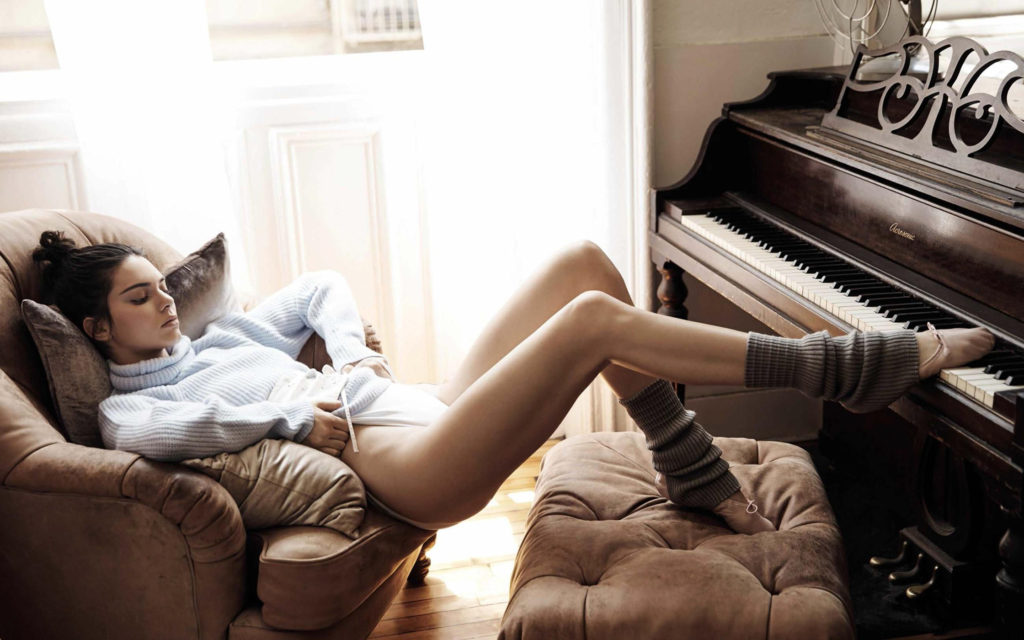 Sexy Photograph of Kendall Jenner slouching in a comfy chair wearing leggings and ballet shoes with one foot touching the keys of a stand up piano
