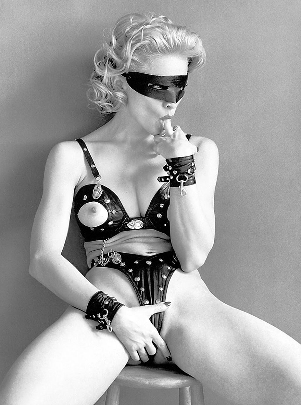 Photograph of Madonna-Dominatrix-Wearing A Mask-Holding Her Crotch and Sucking Her Middle Finger
