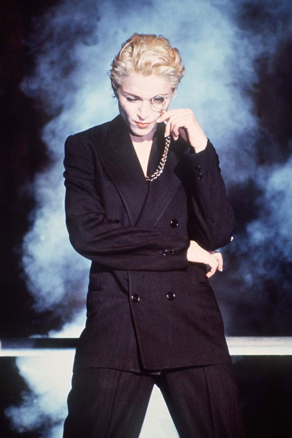 Madonna Gaultier Express Yourself Wearing a Black Suit and Holding a Monocle