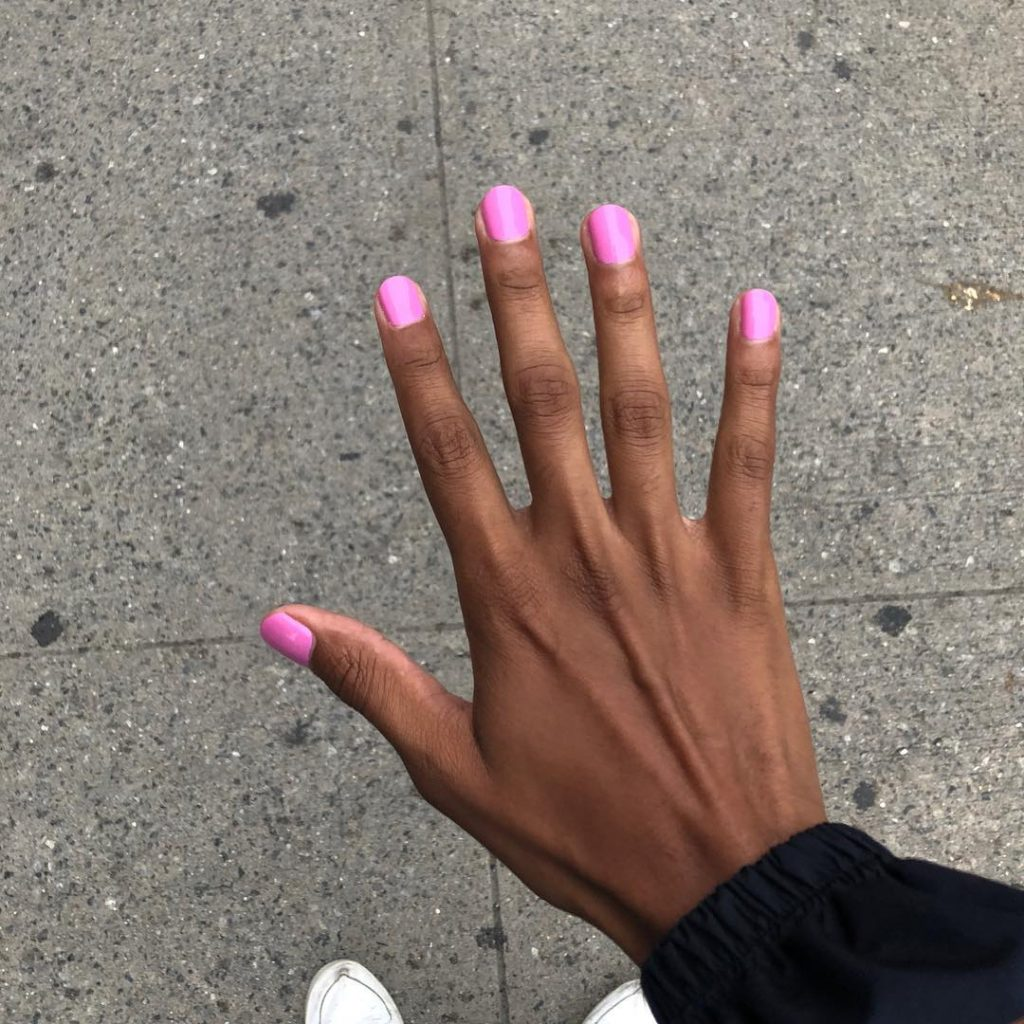 Tyler Mitchell photograph of a women's hand with hot pink painted nails