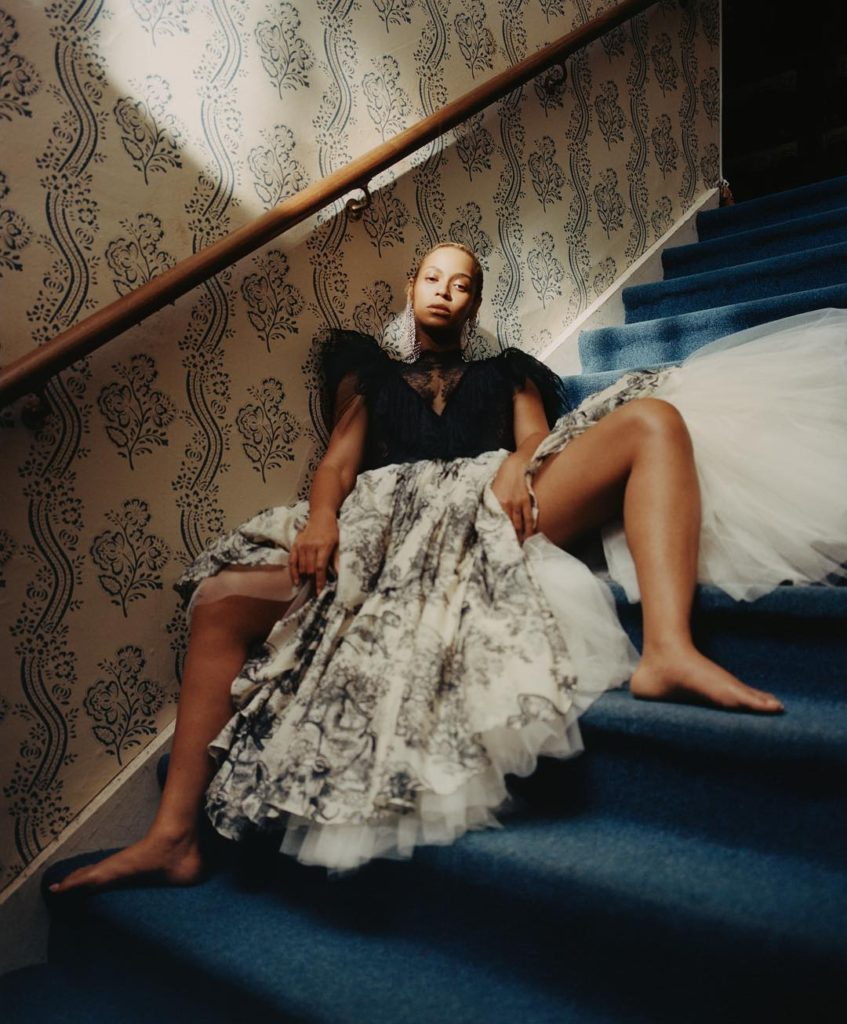 Tyler Mitchell Photograph of Beyonce Sitting on a Blue Carpeted Staircase with bare legs wide open wearing a full white and black printed hoop skirt