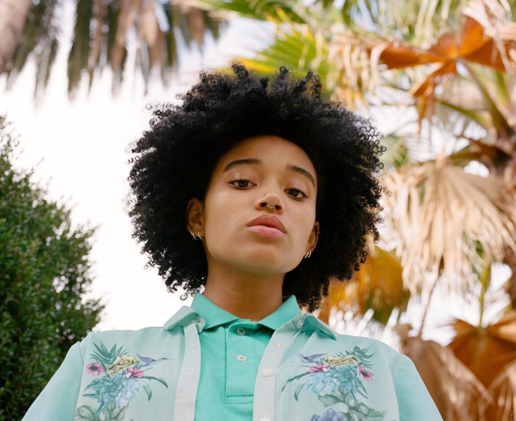 Tyler Mitchell photograph of a Young Model wearing turquoise polo and floral shirt