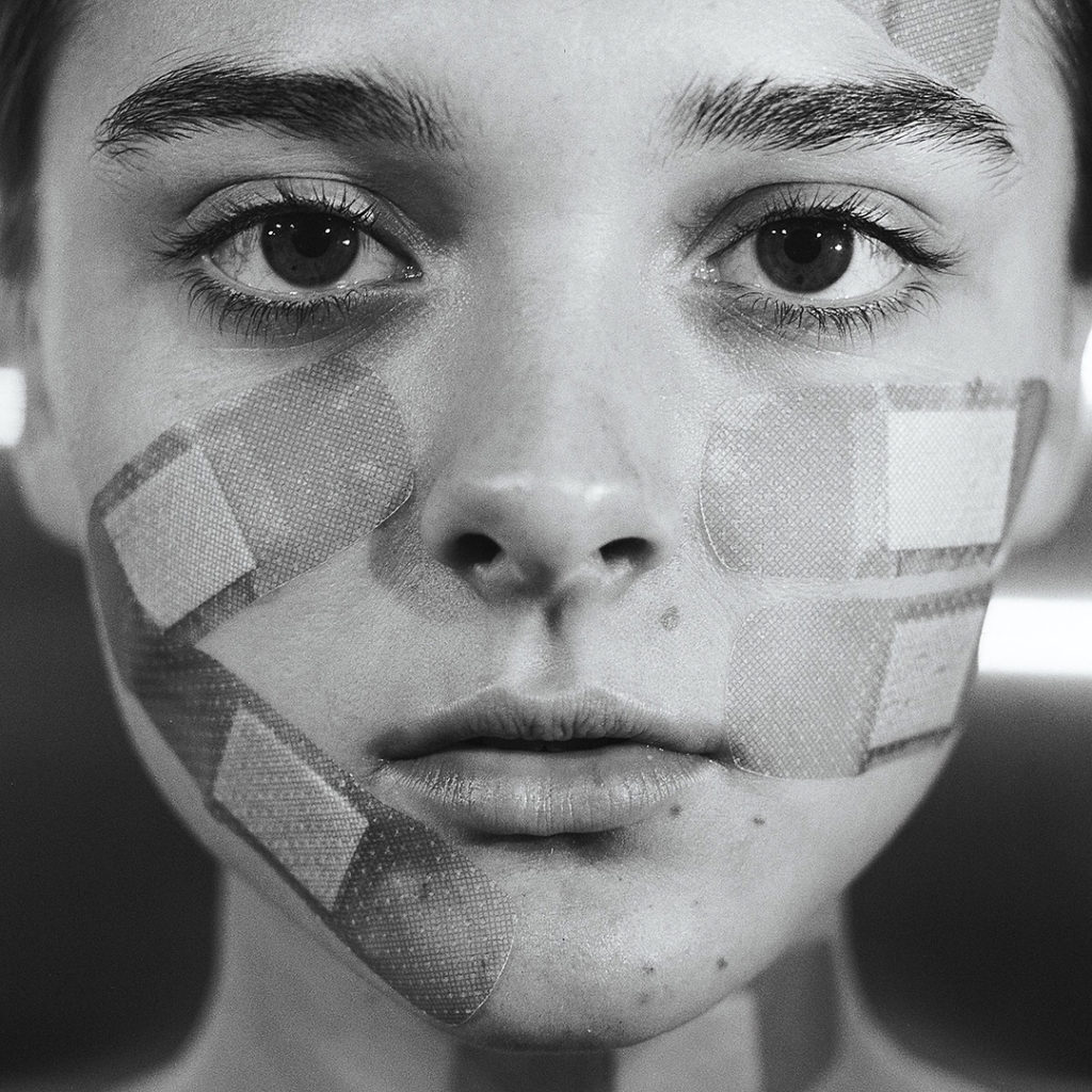 Photographer Tyler Shields photograph of a young girls face covered in large band aids