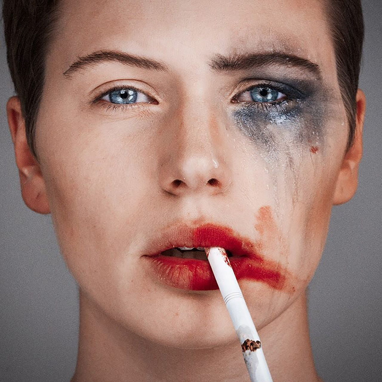 Tyler Shields photograph of a women with one side of her face with smeared make up and a cigarette dangling from her right side of her lip and the left side of her face all clean