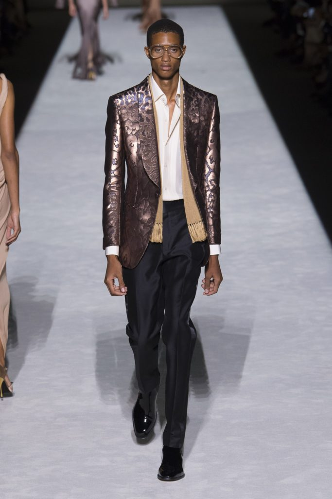 Tom Ford Spring Summer 2019 Runway Male Model wearing a metallic brocade jacket, clear glasses , black pants and beige scarf