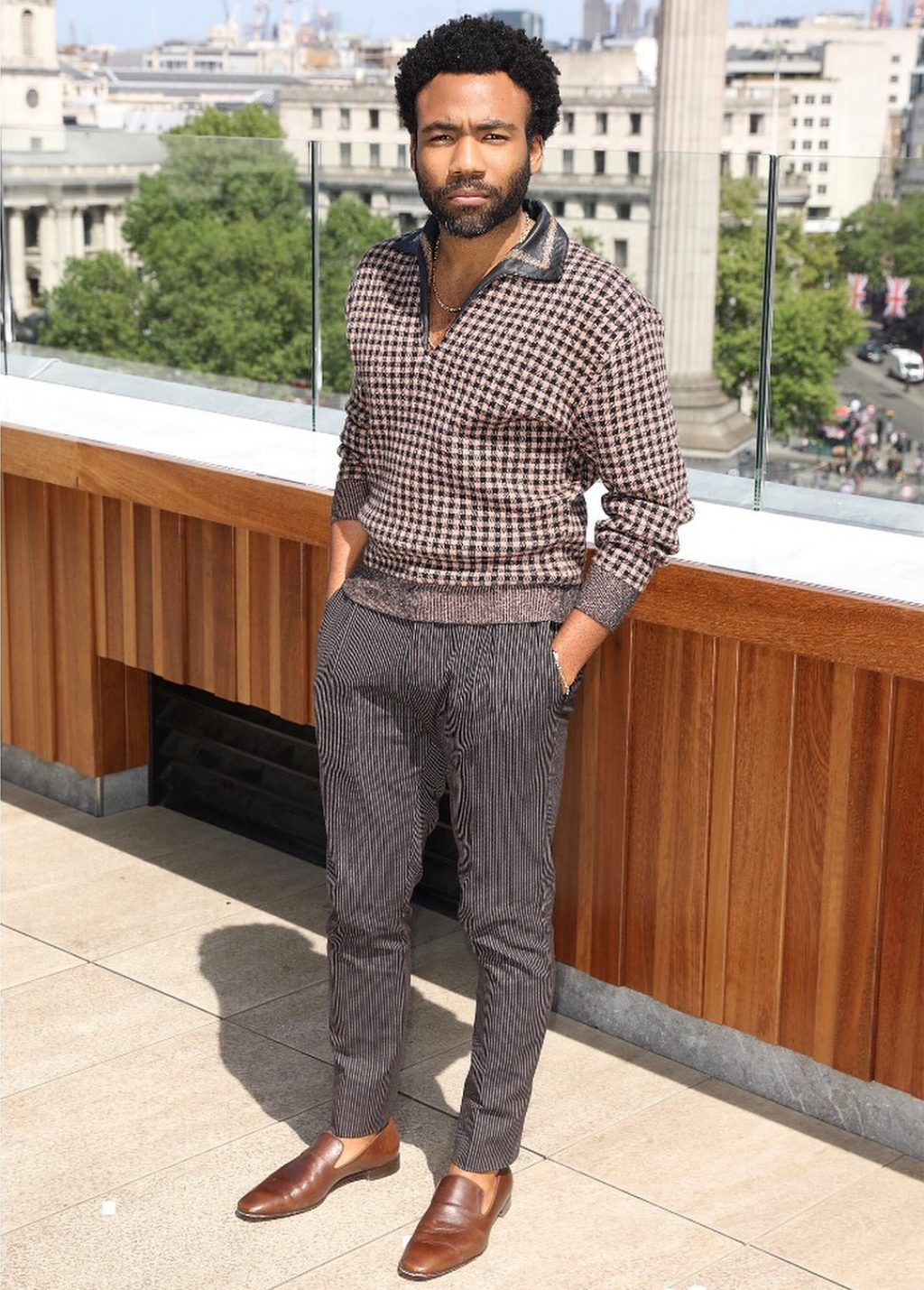 houndstooth knit sweater with a leather-trimmed collar mixed with tweed and stripped trousers accessorized with his signature loafers and no socks.
