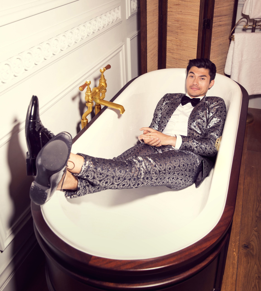 Photograph of Actor Henry Golding Laying in a Tub Wearing a silver metalic suit