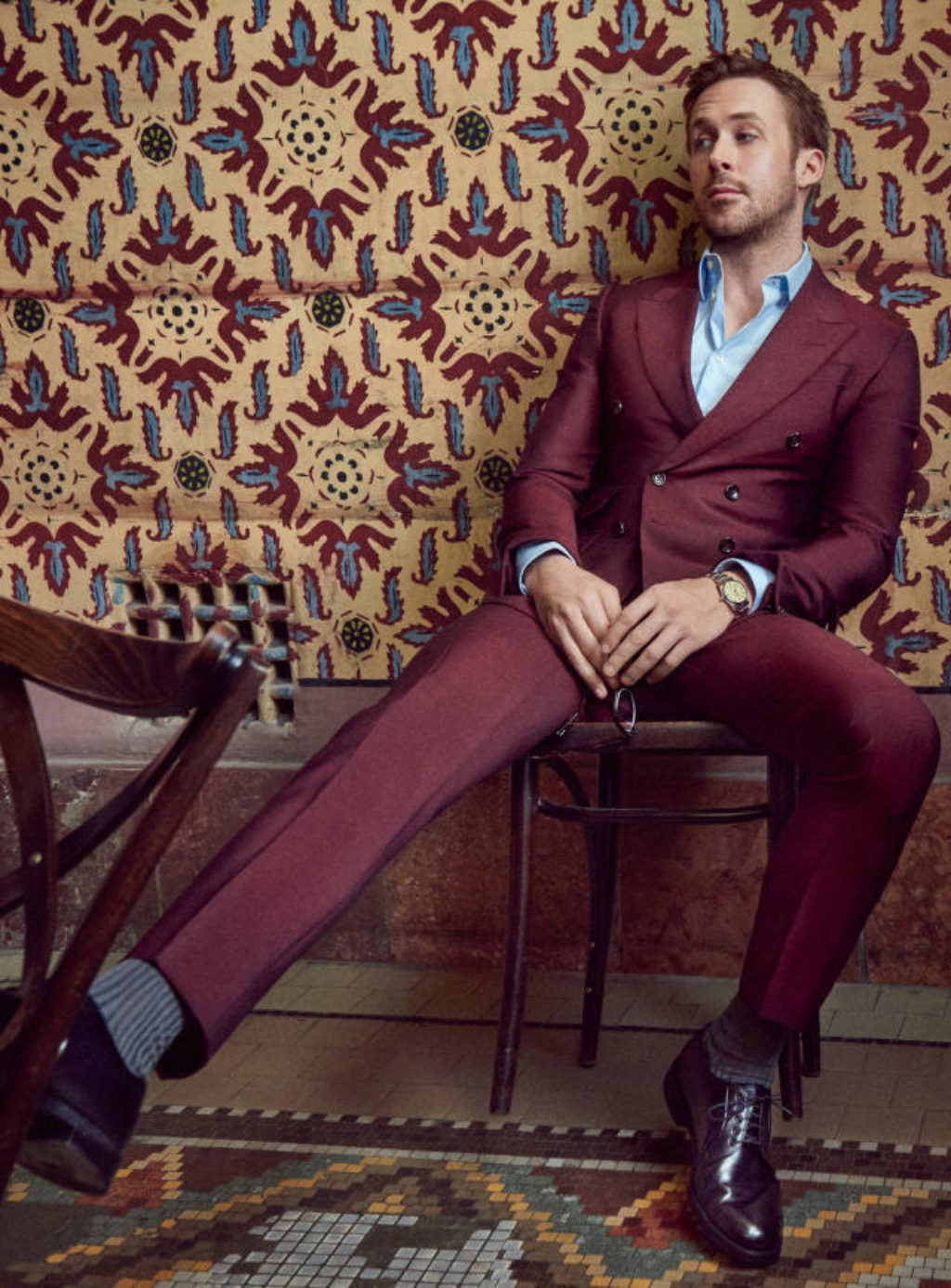 Actor Ryan Gosling in a Cranberry Double Breasted Suit sitting on a wooden cafe chair against a maroon and blue floral tapestry