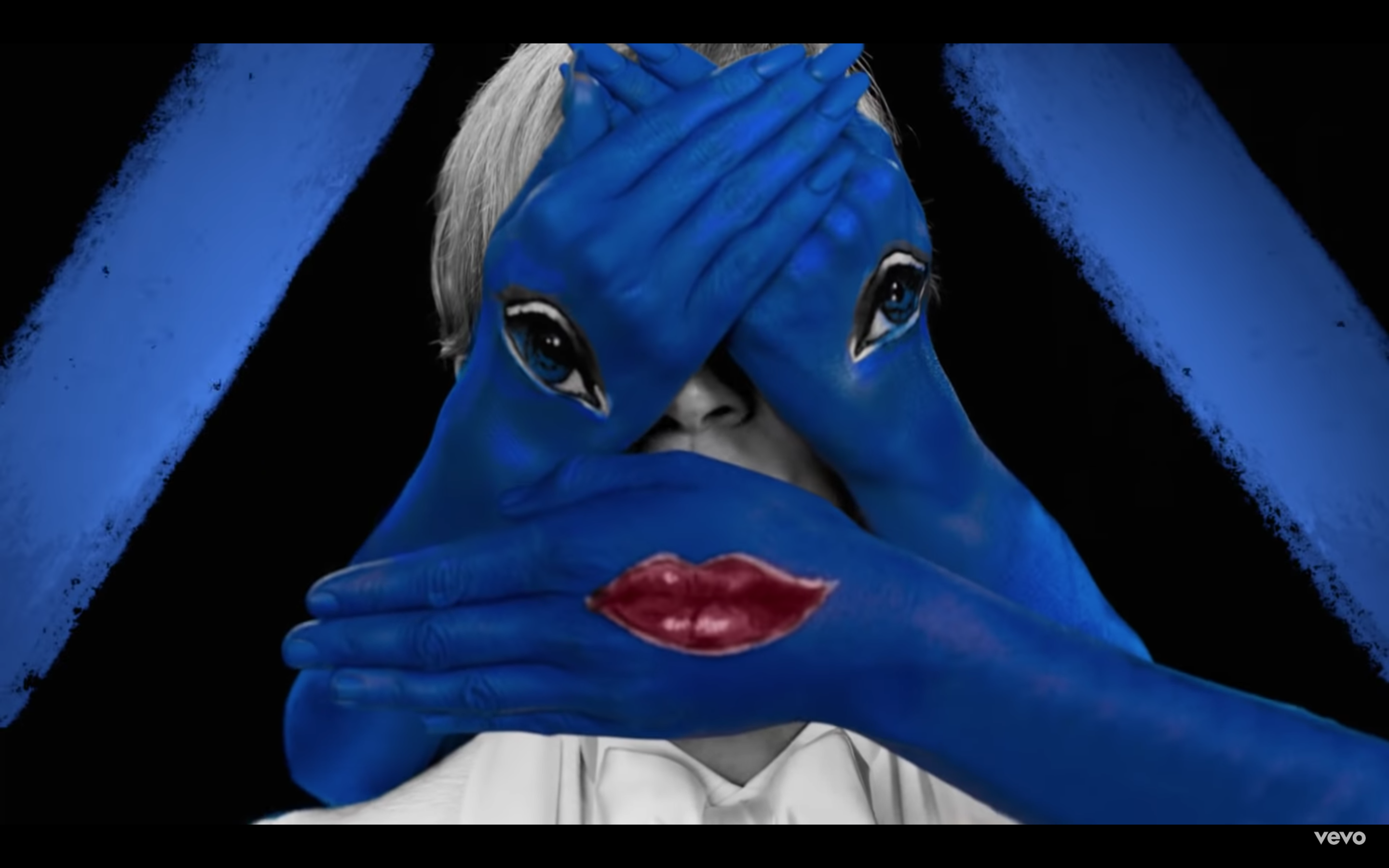 Screen shot of Beck's face hidden by three blue hands: one with lips and the other two with eyes from Beck's New Music Video, Colors, October 2018