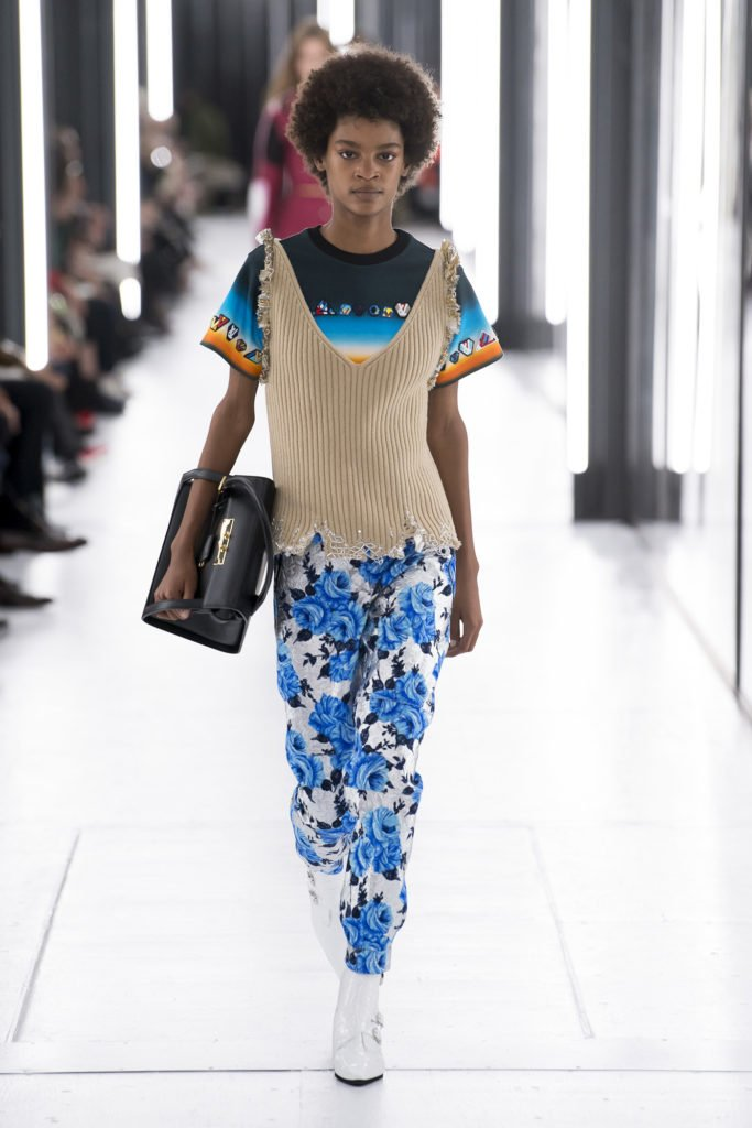 African American Runway Model Wearing Beige Vest, Black, Royal Blue and Orang Short-Sleeve Shirt, White Pants with Blue and Black Floral Pants and White Patent Leather Pointy Ankle Boots with Buckle