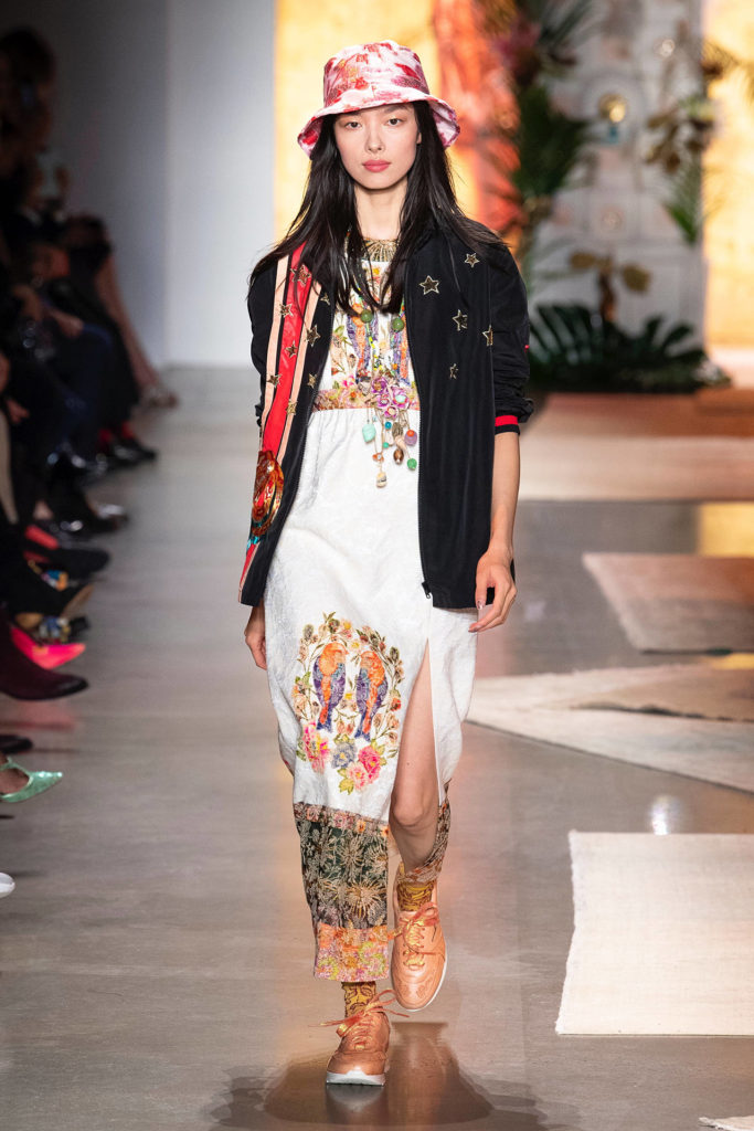 Asian Female Runway Model Wearing Red and White Hat, Black Blazer with Red and White Stripes on Left Side and Stars on the Right side over a shite peasant dress with 2 colorful birds and orange sneakers