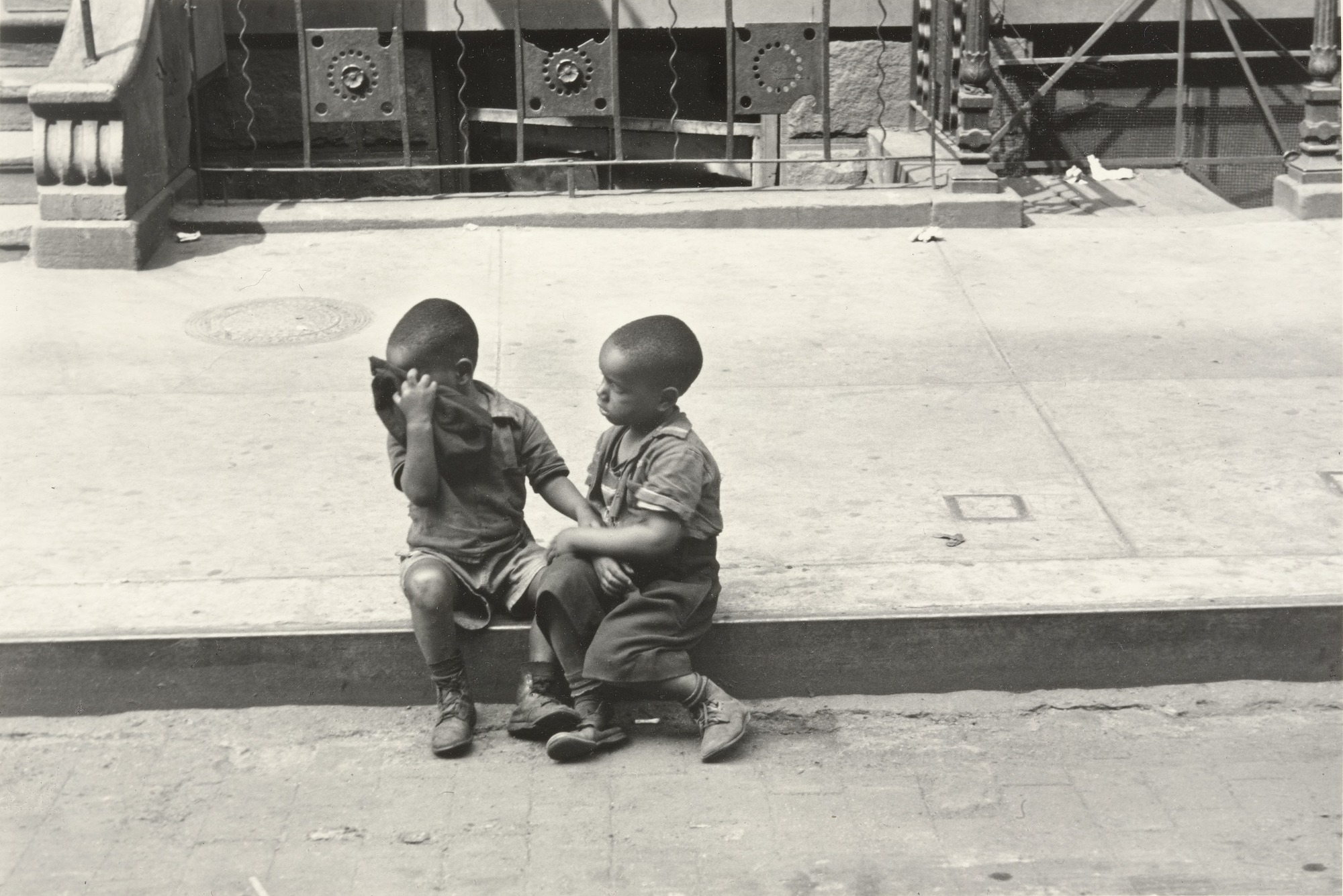 Two boys sitting on a curb in New York