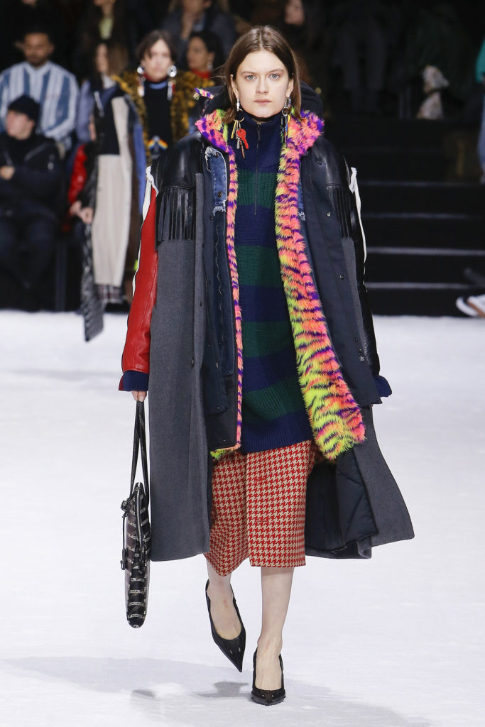 Female Runway Model Wearing Gray Coat with Black Leather Trim on the shoulders, blue and green zipper sweater, pink, purple and yellow fur jacket and red checked skirt-Balenciaga Collection