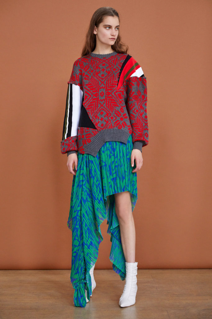 Female model wearing Red and Grey Norwegian Print Sweater with Black and White Striped Left Sleeve, Green and Blue Sarong and white ankle boots by Preen by Thornton- Bregazzi-Resort 2019