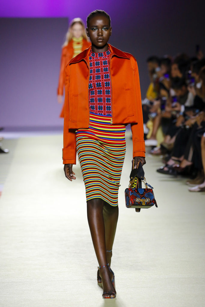 African American Female Runway Model wearing and orange jacket, red and blue block print top, red, yellow and blue pencil skirt carrying a mini tote
