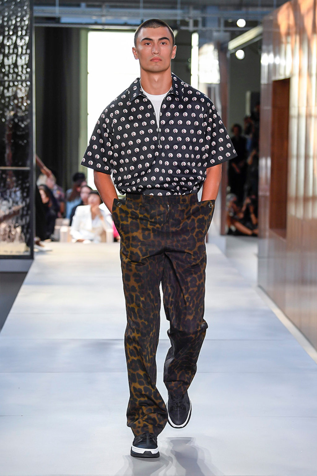 Male Runway Model Wearing Brown Leopard Print Pants and Black Short Sleeve Shirt with White Polka Dots-Burberry Men's Collection