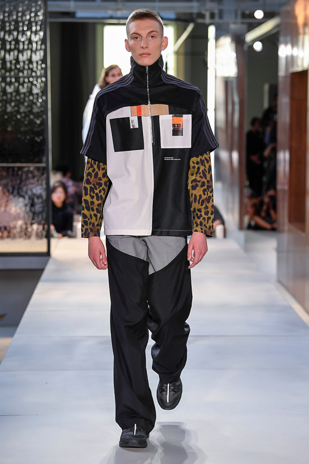 Male Runway Model Wearing short sleeve jacket half white and half black with black and white pockets, orange accents, brown and black leopard print sleeves, black and gray geometric pants-Burberry Men's Collection 2019