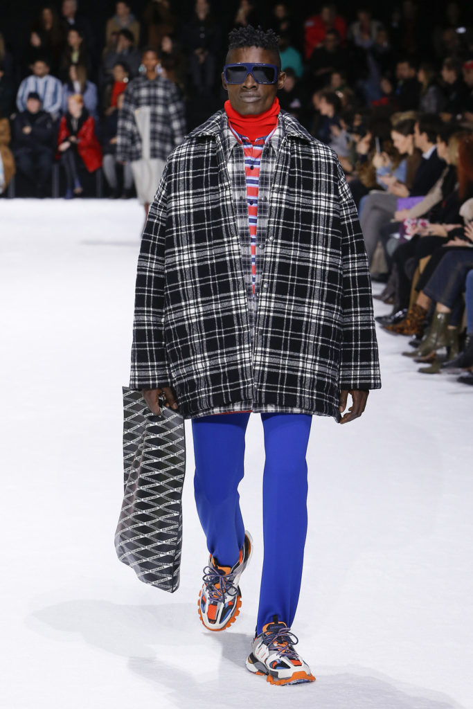 African American Male Runway Model Wearing Cool Blue Sunglasses, Red Turtleneck, red, blue and white striped shirt, black and white extra big shirt jacket, royal blue pants and orange and blue trainers