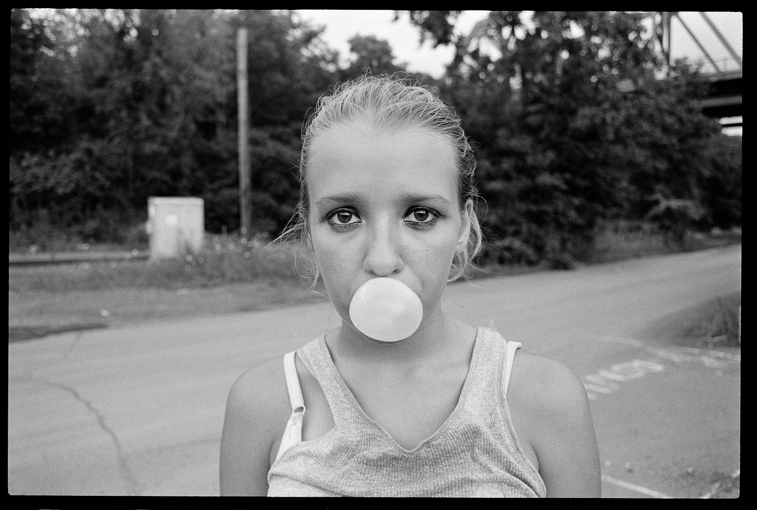 Teen blows bubble with gum