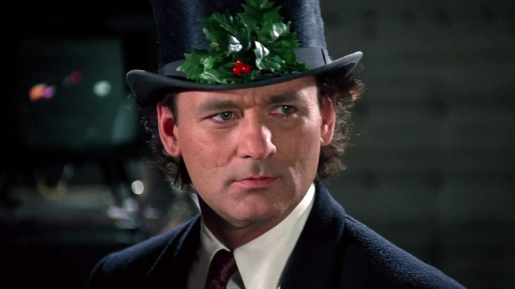 Billy Murray in the film Scrooged wearing a black top hat, holly leaves and red berries