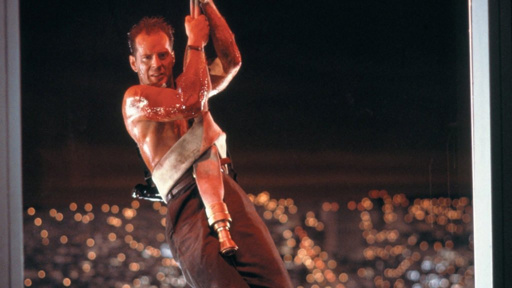 Bruce Willis in Die Hard shirtless, bleeding and repelling down the building on a fire hose wrapped around his stomach