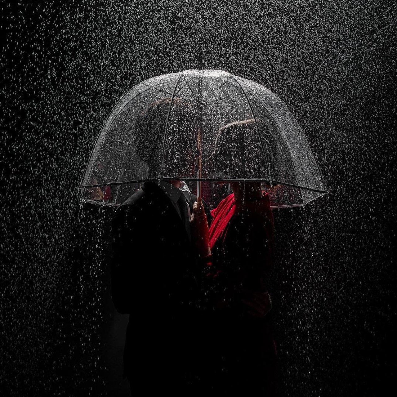 artistic image of couple under an umbrella in the rain at night
