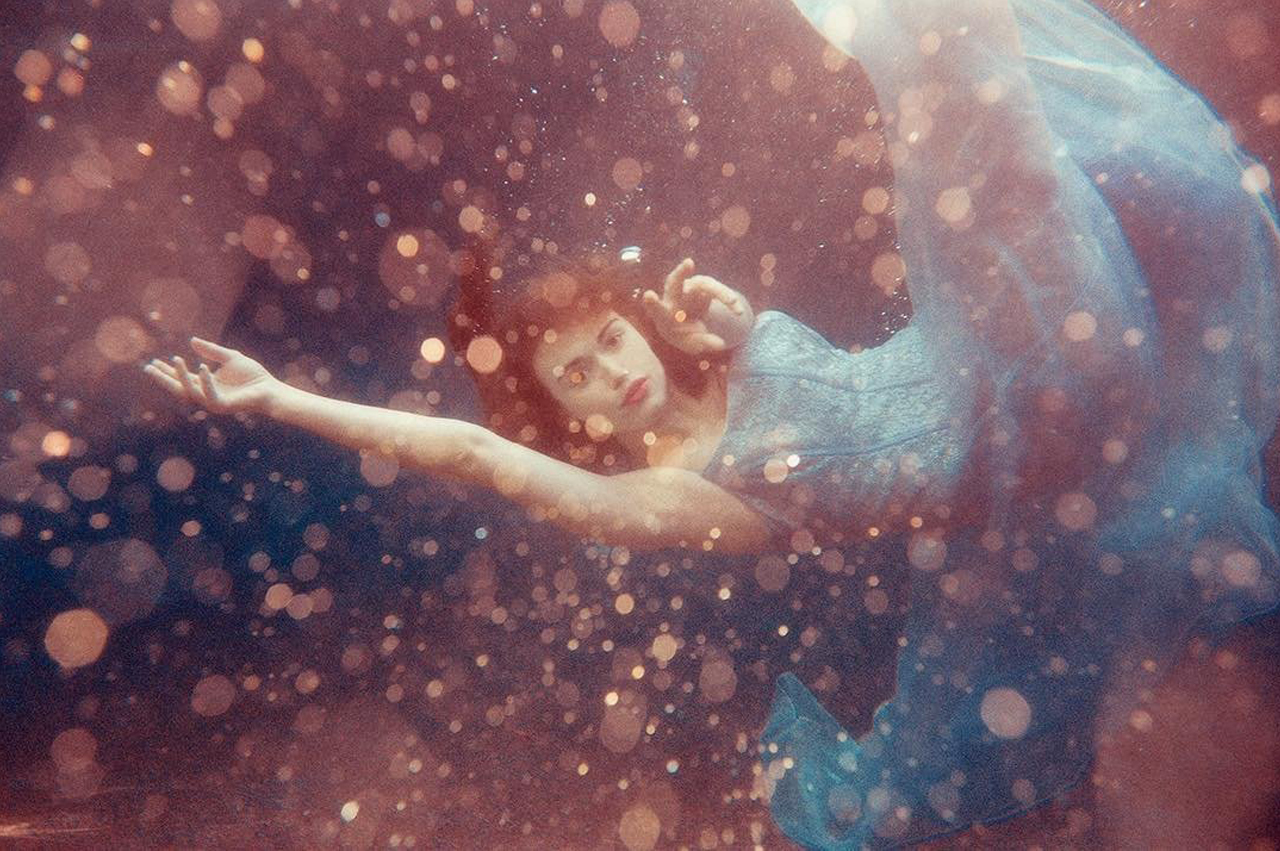 woman in dreamscape wearing a gown underwater