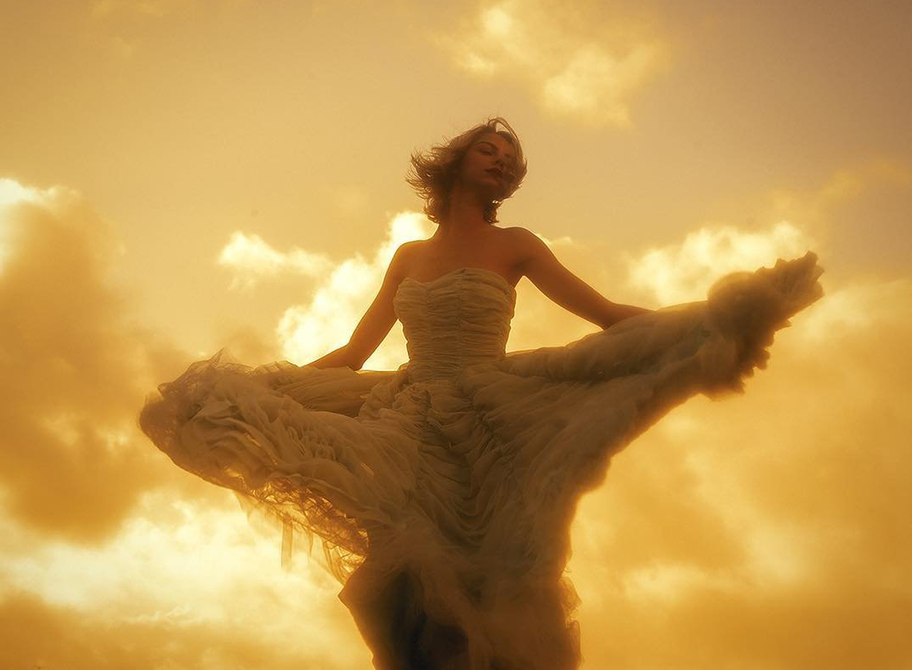 image of woman in a gown dancing at sunset
