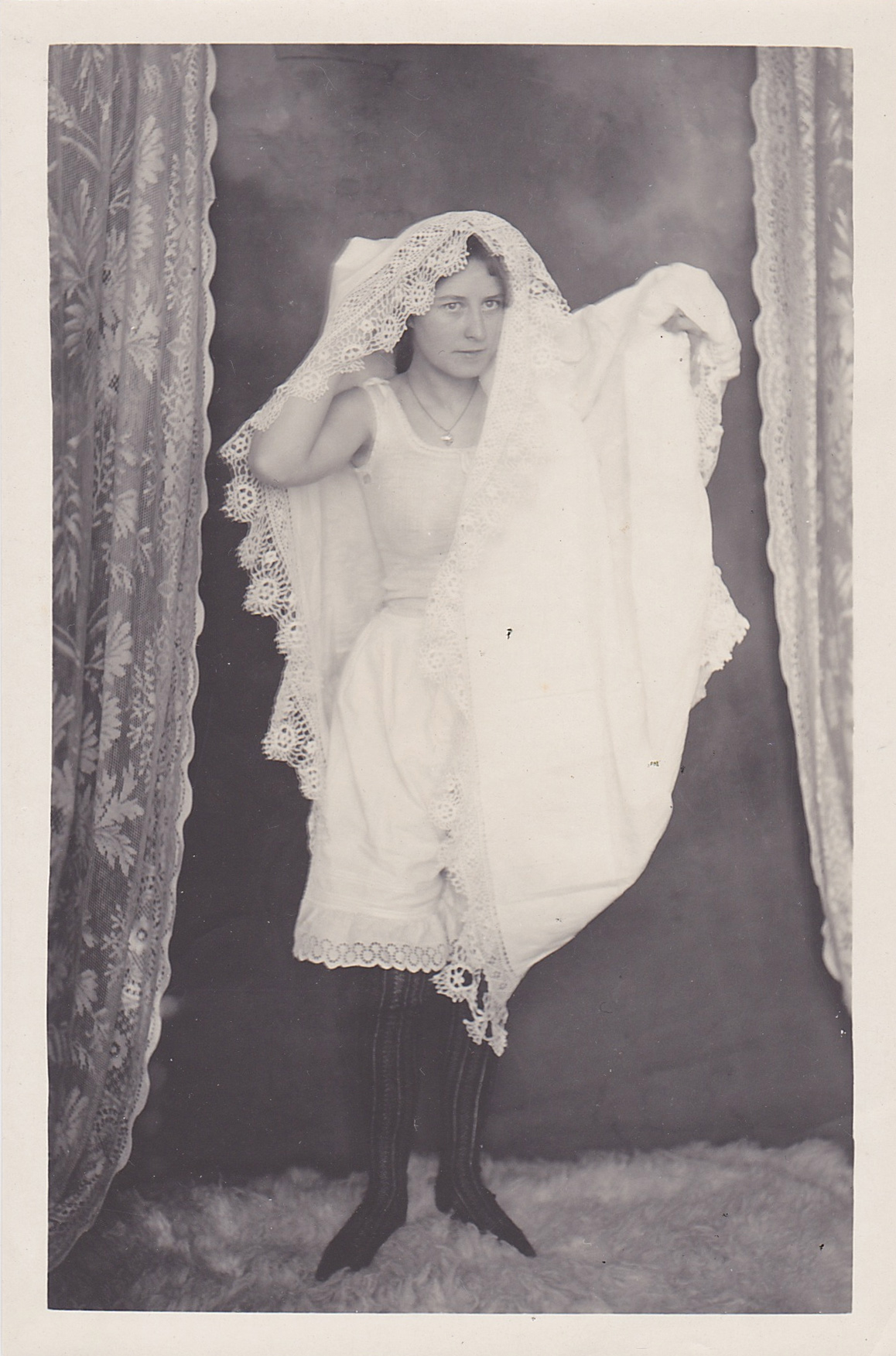 antique photo of a woman wearing underwear and a tablecloth