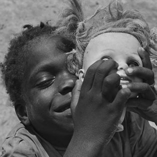 Photograph of an African boy holding a dolls head shot by Eugene Richards