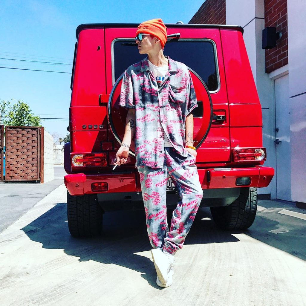 Nats Getty Wearing Hand Painted Pajama Set In Front of Her Red MBZ Land Cruiser