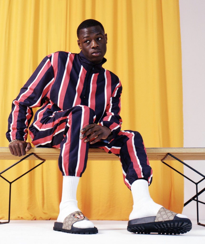j-hus-wearing-asos-blue-red-and-white-striped-jacket-and-pants-white-crew-socks-and-slides