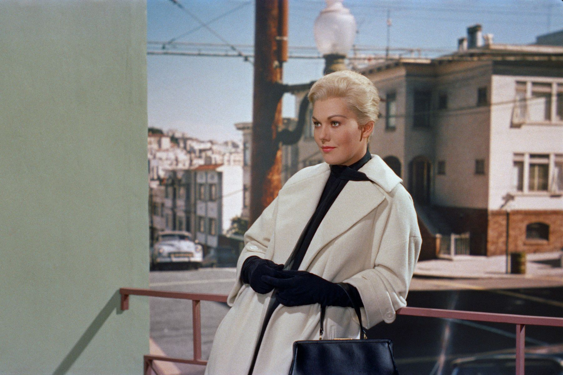 blonde, upperclass woman leans on a railing while wearing a white coat