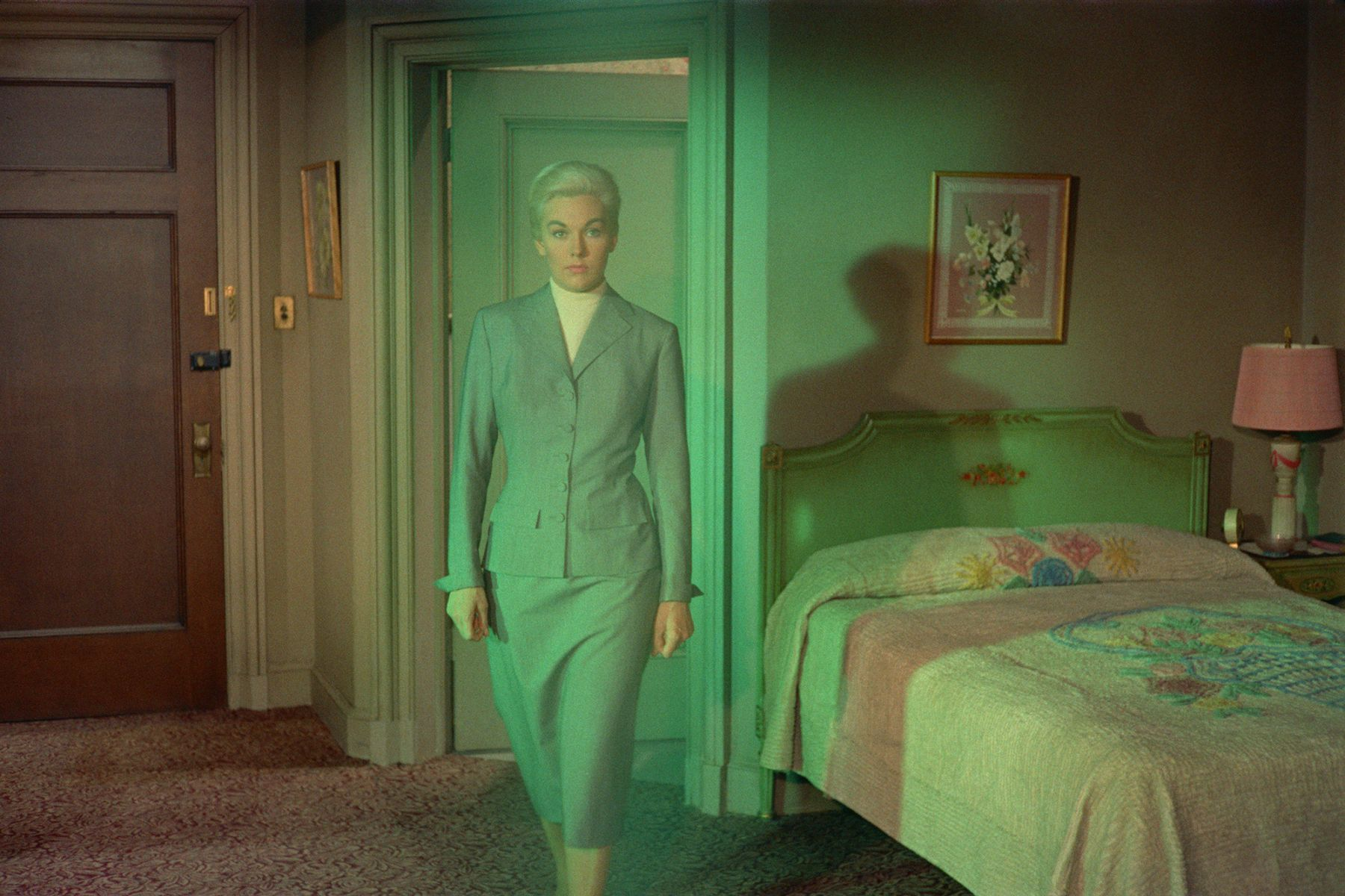 apparition of a woman in a skirt suit walks through a bedroom